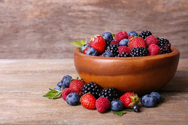 Frutos maduros e doces diferentes em uma tigela, na velha mesa de madeira
