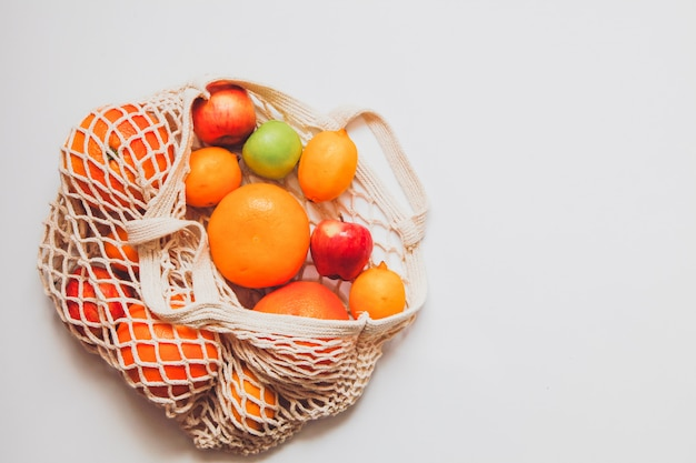 Frutos maduros no saco de rede de crochê no espaço em branco. conceito de estilo de vida saudável. conceito de entrega.