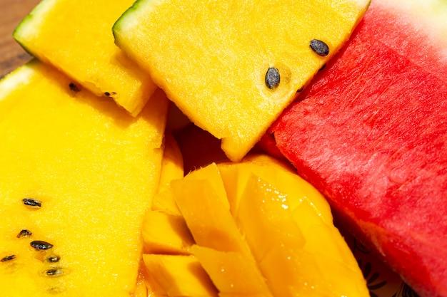 Frutos maduros suculentos maduros do close up da manga e da melancia vermelha e amarela. prato de frutas doces e coloridas