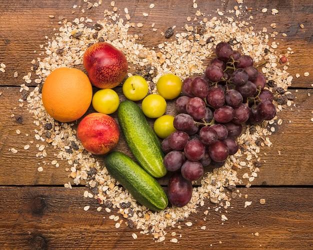 Frutos saudáveis entre forma de coração feita com aveia e porca comida na mesa de madeira
