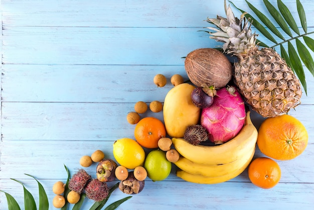 Frutos sazonais do verão tropical suculento maduro na folha de palmeira no fundo de madeira azul.