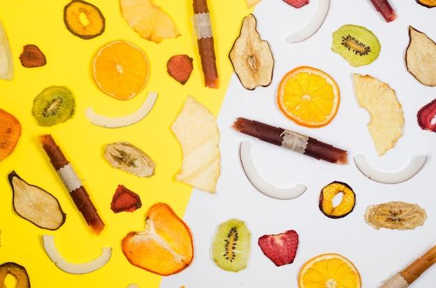 Frutos secos agregados, salgadinhos espalhados em fundo branco e amarelo. batatas fritas de frutas. conceito de alimentação saudável, lanche, sem açúcar. vista superior, copie o espaço.