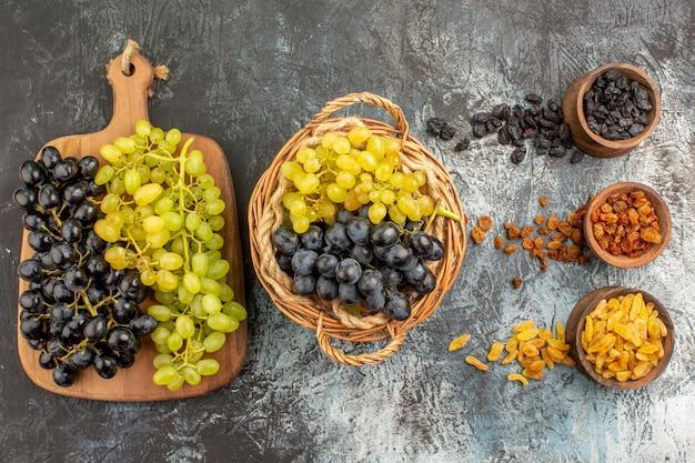 Frutos secos as uvas apetitosas no cesto e no tabuleiro frutos secos