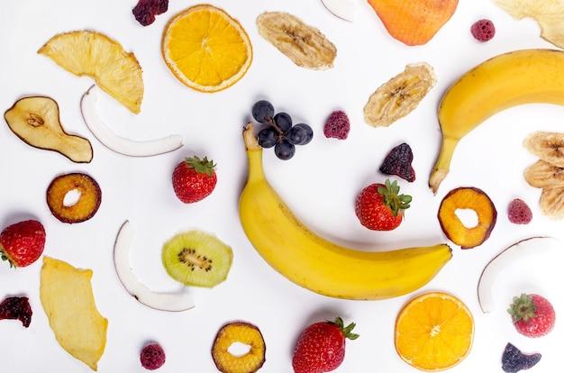 Frutos secos associados, chips espalhados no fundo branco. batatas fritas de frutas. conceito de alimentação saudável, lanche, sem açúcar. vista superior, copie o espaço.