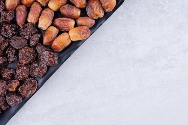 Frutos secos com tâmaras e cerejas numa travessa de madeira. foto de alta qualidade
