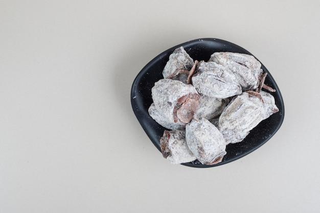 Frutos secos de caqui em tigela preta