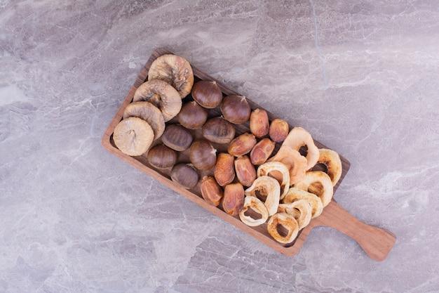 Frutos secos e bagas numa bandeja de madeira.