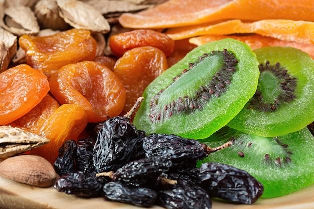 Frutos secos e nozes. natureza morta em uma placa de madeira redonda.