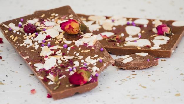 Frutos secos e pétalas de rosa na barra de chocolate comido