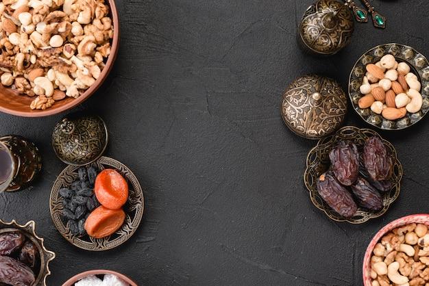Frutos secos frescos; nozes e datas para o ramadã em pano de fundo preto