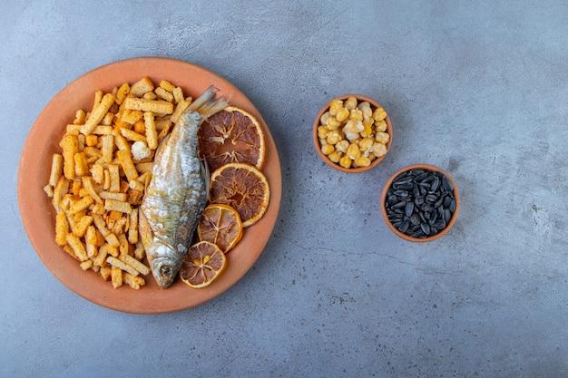 Frutos secos, peixe e pão torrado num prato junto a tigelas de grão-de-bico e sementes, na superfície de mármore.