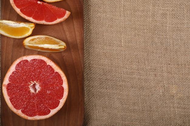 Frutos torpical cortados em uma placa de madeira em um pedaço de serapilheira.