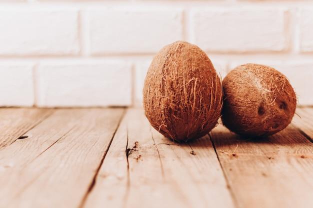 Frutos tropicais de coco em uma mesa de madeira contra um fundo de parede de tijolo.