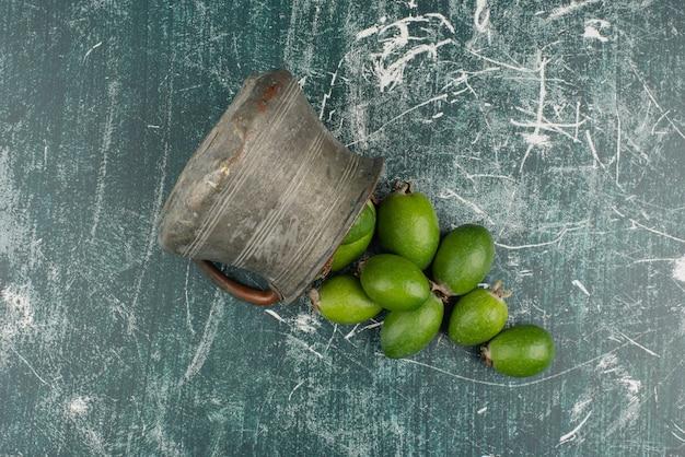 Frutos verdes de feijoa caindo do vaso na superfície de mármore.