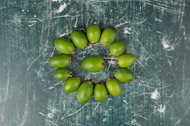 Frutos verdes de feijoa em superfície de mármore.