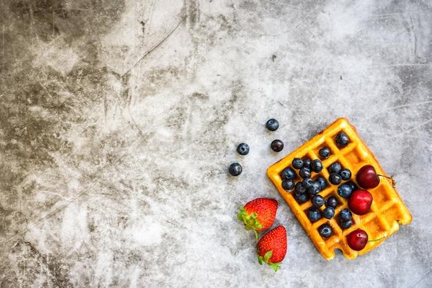 Frutos vermelhos sazonais maduros, saborosos em um waffle para o café da manhã