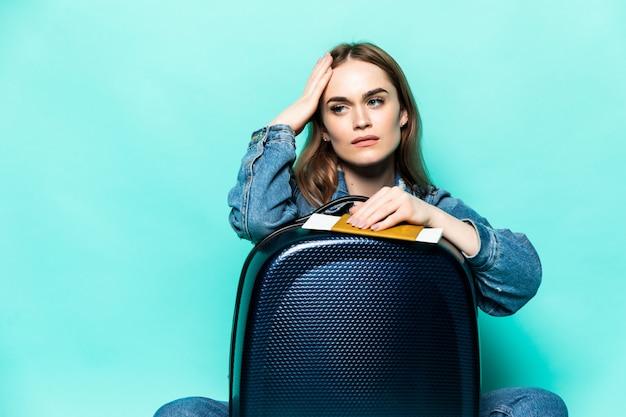Fuca caucaiana europeia vestida com roupas de verão, sentado na mala com bilhetes de avião, sonhando com voo e viagem, isolado na parede verde