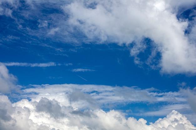 Fuga do avião no céu nebuloso azul.