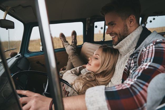 Fugindo de tudo ... mulher jovem e atraente descansando e sorrindo enquanto o namorado dirigia uma minivan estilo retro