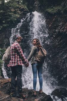 Fugindo de tudo ... retrovisor de corpo inteiro de um jovem casal de mãos dadas em pé perto da cachoeira