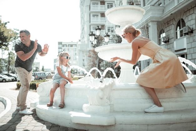Fugindo do calor. menina alegre e seus pais molhados brincando com respingos de água da fonte.
