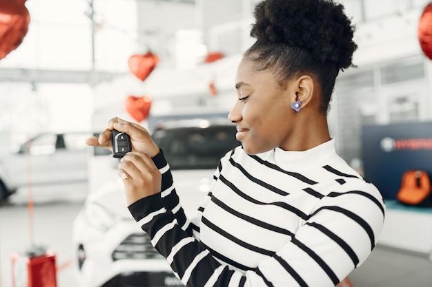 Fui fazer compras hoje. foto de uma atraente mulher africana mostra as chaves da câmera.