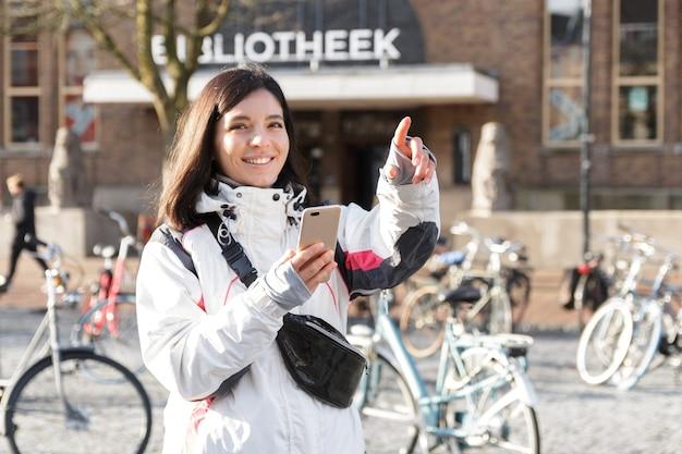 Fuja em uma cidade. mulher jovem de etnia no início da primavera, usando um telefone para se orientar nas ruas.