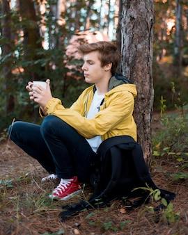 Full shot adolescente sentado no chão perto de uma árvore