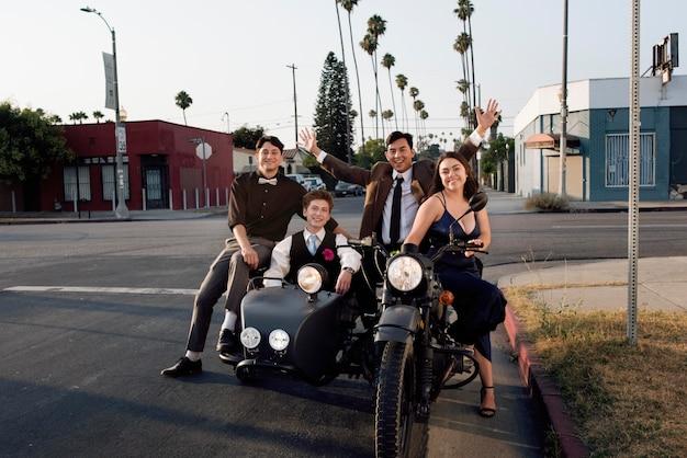 Full shot amigos felizes com motocicleta