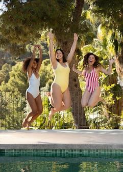 Full shot amigos felizes na piscina