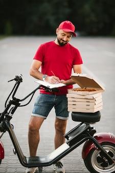 Full shot delivery guy escrevendo na área de transferência