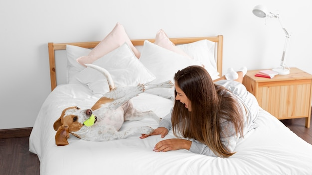 Full shot garota na cama com cachorro