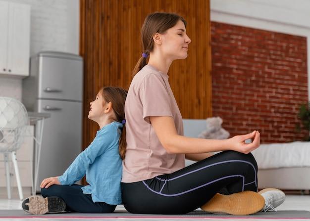 Full shot mãe e filho meditando