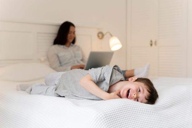 Full shot mãe e filho na cama