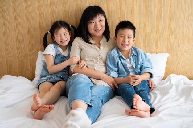 Full shot mãe e filhos na cama
