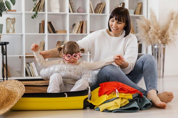 Full shot mãe e menina com bagagem