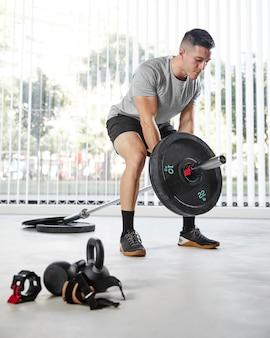 Full shot man treinando com peso dentro de casa
