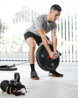Full shot man treinando com peso