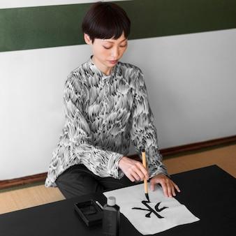 Full shot mulher asiática pintando carta