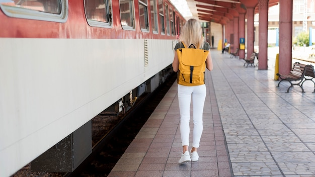 Full shot mulher com mochila caminhando ao longo do trem