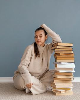 Full shot mulher com pilha de livros