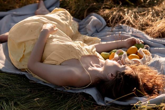 Full shot mulher deitada em um cobertor com frutas