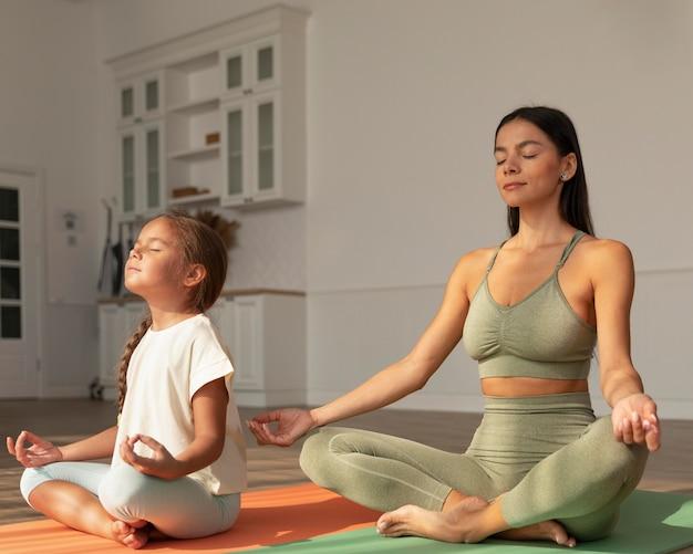 Full shot mulher e criança meditando em casa