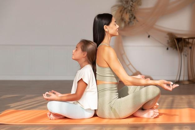 Full shot mulher e criança meditando