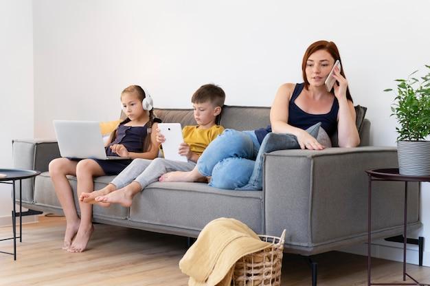 Full shot mulher e crianças com dispositivos
