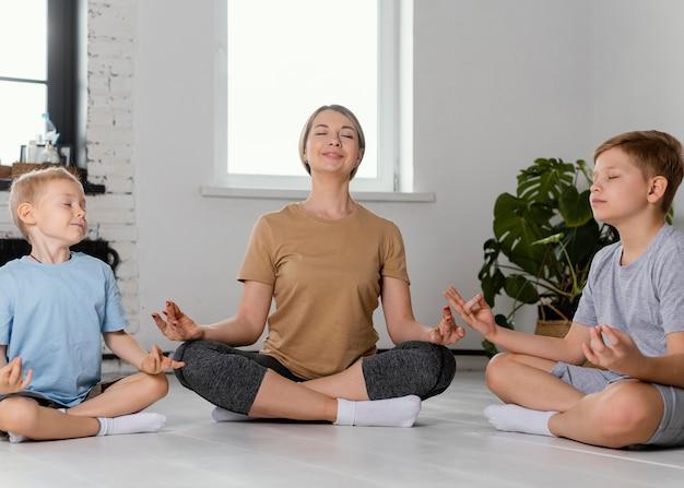 Full shot mulher e crianças meditando