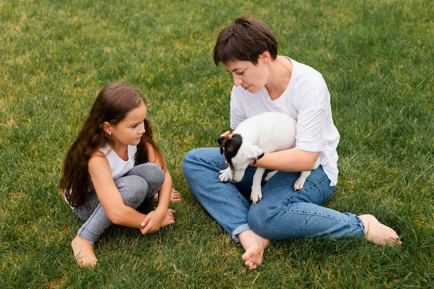 Full shot mulher e menina com cachorro