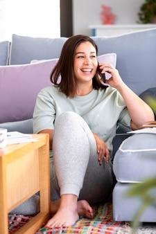 Full shot mulher falando ao telefone