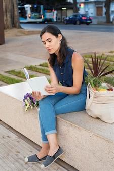 Full shot mulher lendo ao ar livre