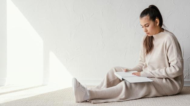Full shot mulher lendo livro no chão